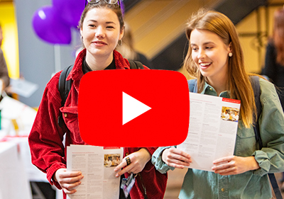 Image of two female students at Preview Day with a play button superimposed. The image acts as a link to a slide show of Grad Studies Preview Day 2018